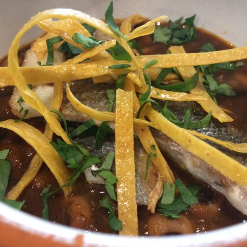 Guiso mexicano de alubia carilla con merluza asada y totopos fritos.