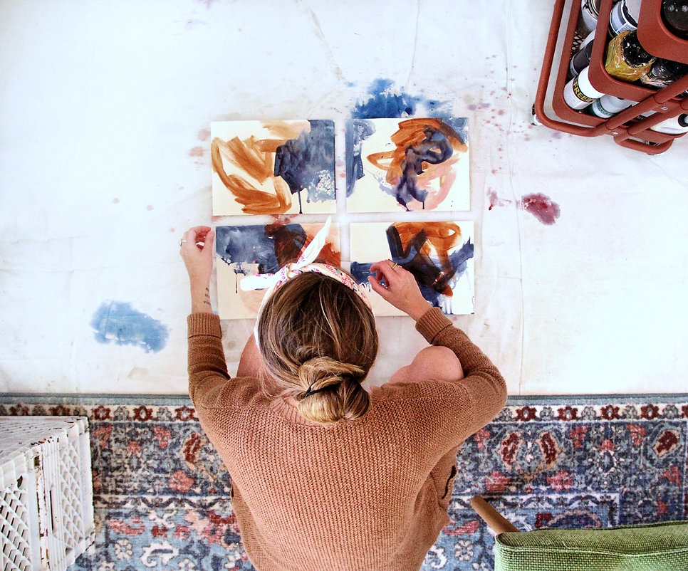 Overhead shot of artist spreading out watercolor paintings on the studio floor