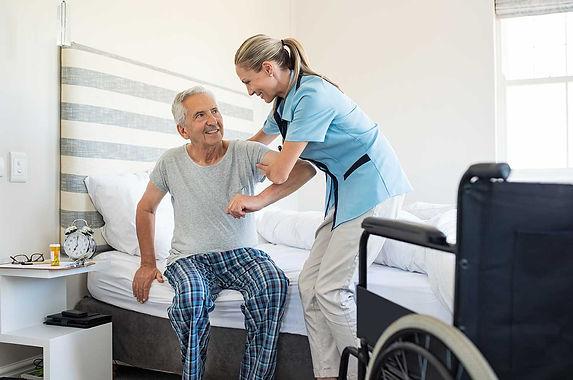 nurse-helping-old-patient-get-up-MJXB65R