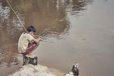 Young kid fishing in the Amazon Rainfore