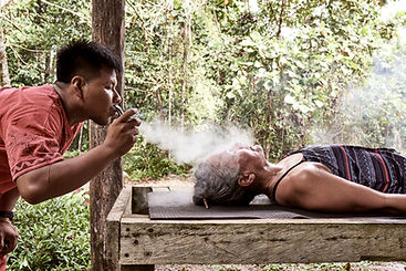 Urias Shipibo Curandero blowing Mapacho