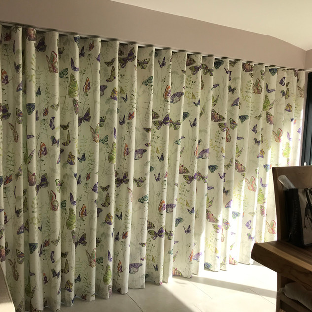 Wave headed curtains fitted inside the recess on a discreet ceiling fixed track