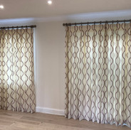 A pair of curtains with double pinch pleat heading on colour co-ordinated wooden poles