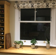 Crewel work fabric blind in a kitchen