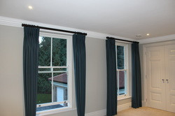 Wool curtains with pinch pleat heading on bespoke pole with uplift brackets