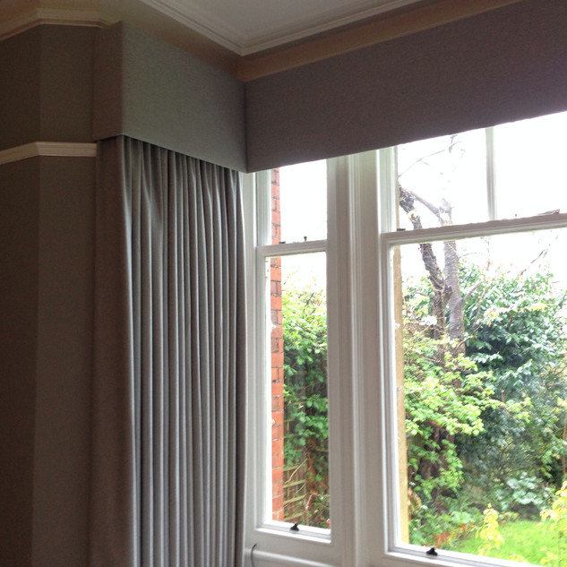 Grey wool curtains with matching pelmet in a square bay