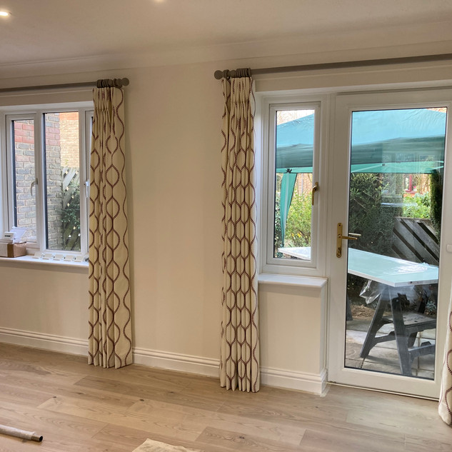 A pair of curtains on colour co-ordinated wooden poles