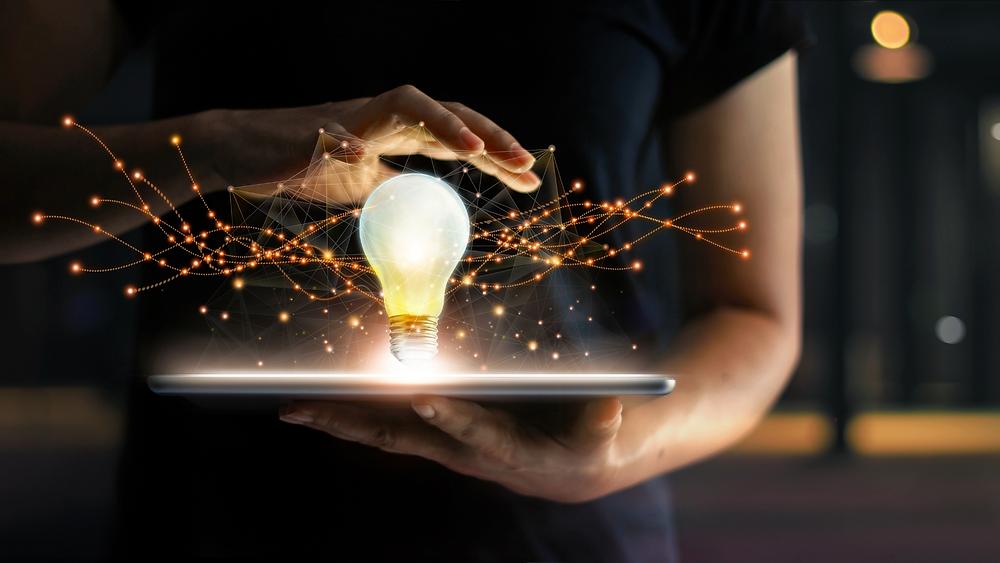 inovação em tecnologia onde mulher segura um tablet com uma lâmpada acesa