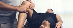 Therapist treating injured knee of athlete male patient - sport physical therapy concept,