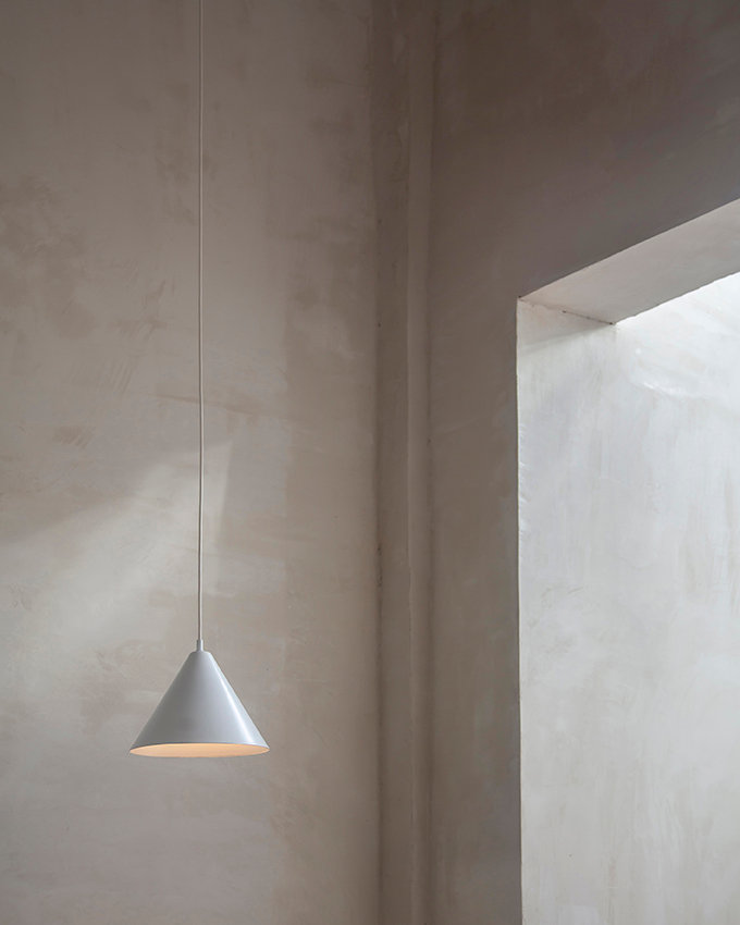a interior design detail shot of opa restaurant designed by craft and bloom in tel aviv, israel. natural plaster wall with minimalistic pendant light