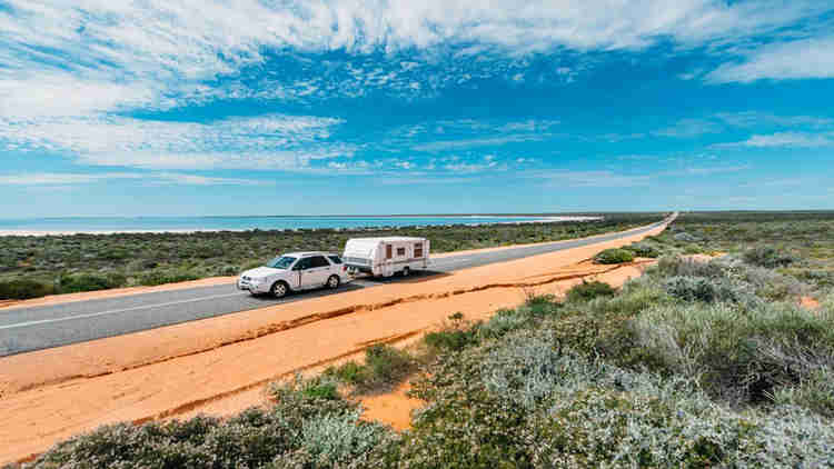 white car pulling caravan near ocean