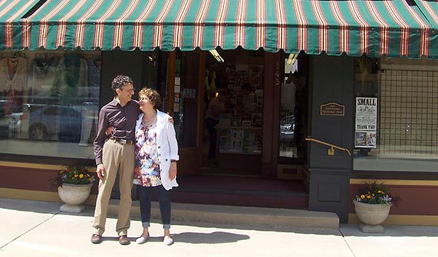 Joel Marcus & Judy Swartz Marcus standing in front of Nina's Department & Variety Store