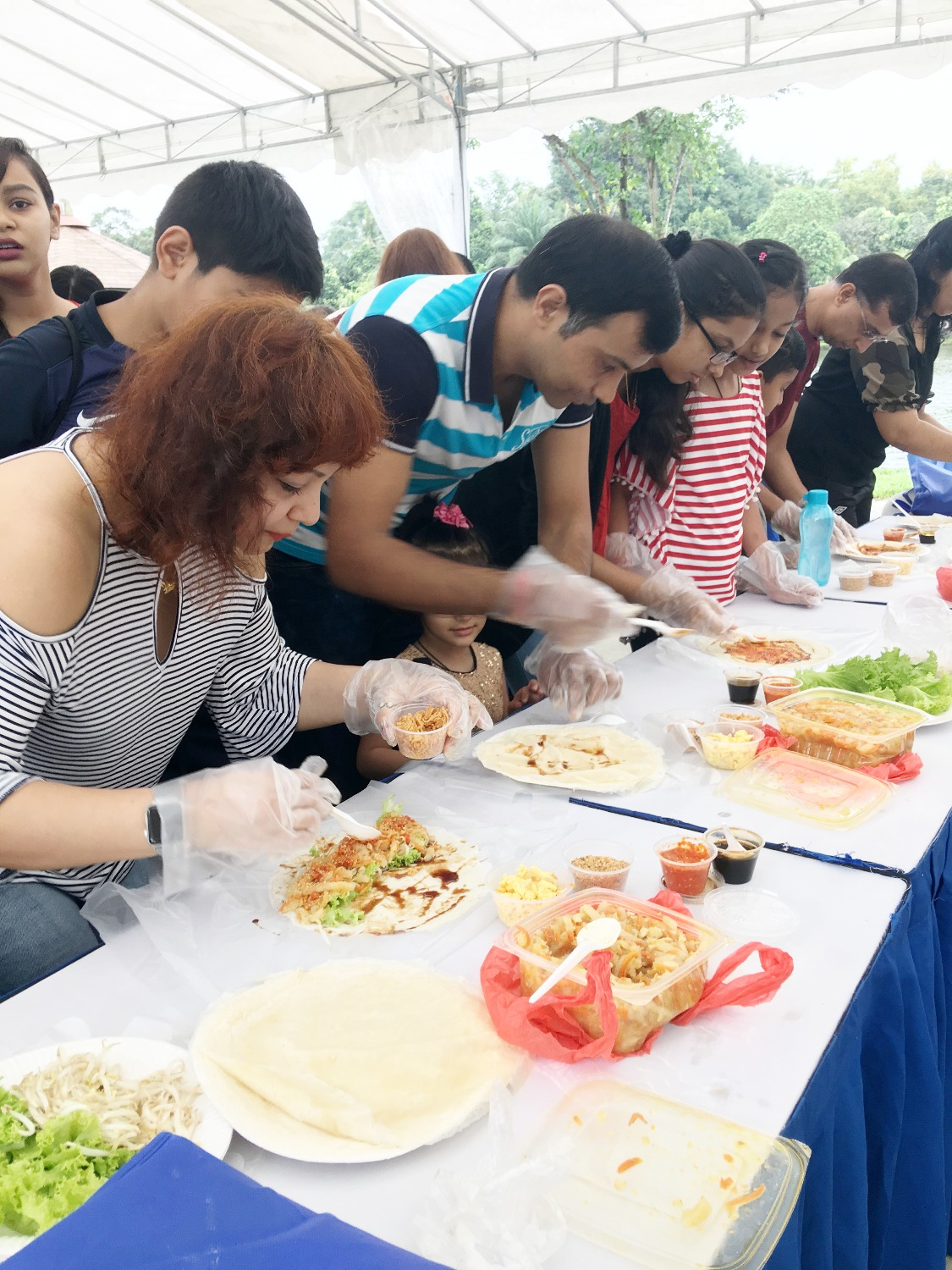 Families having fun making popiah
