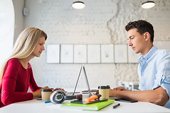 young-man-woman-sitting-table-face-face-working-laptop-co-working-office_285396-1730.webp