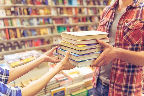 Une femme donne une pile de six livres à un homme dans une librairie