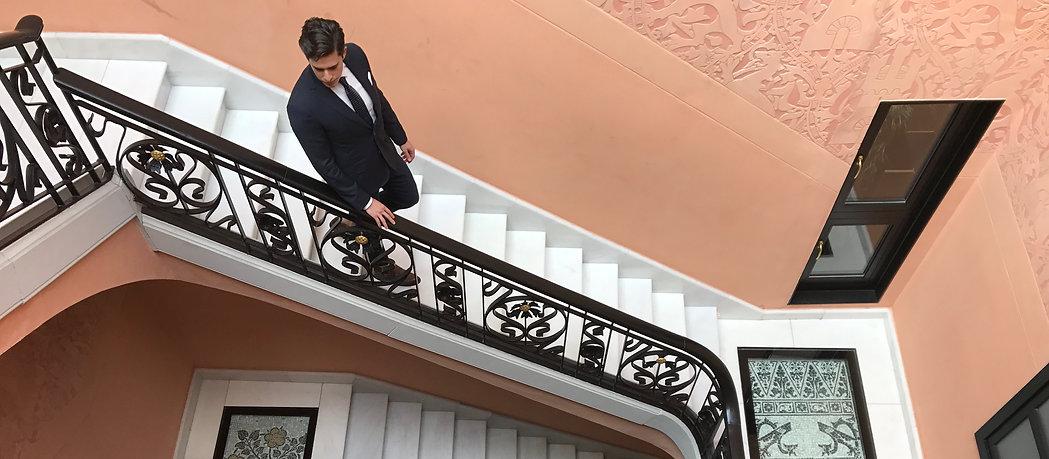 Man in suit walking down stairs