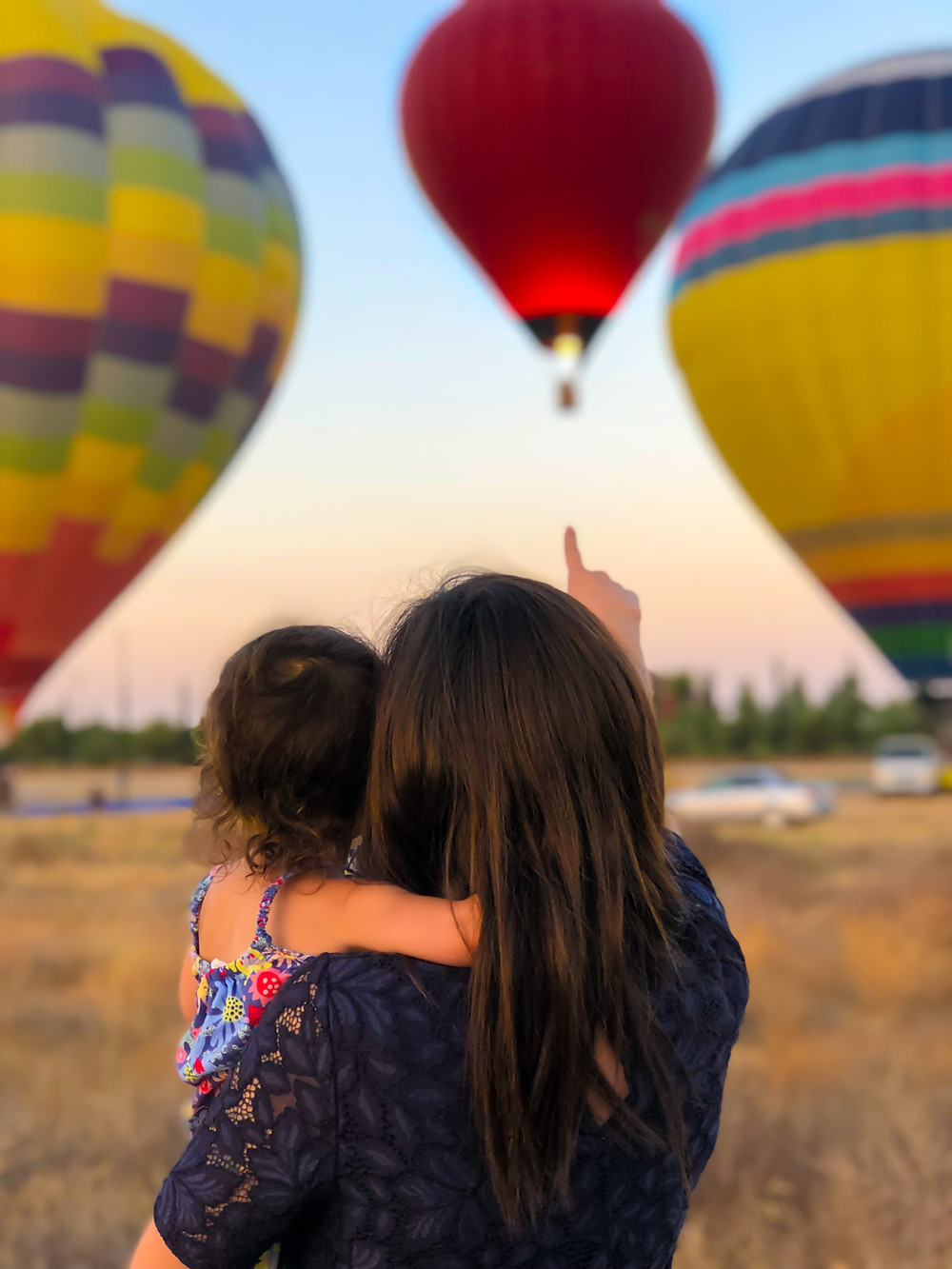 A mother holds her child and watches hot air balloons.