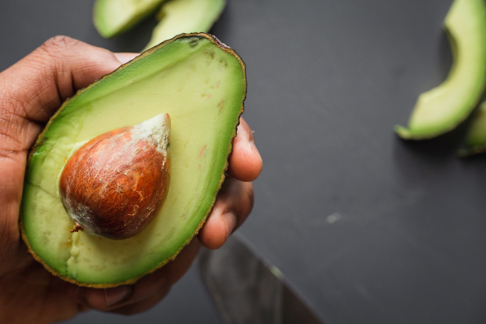 Hand holding an avocado that has been sliced in half.