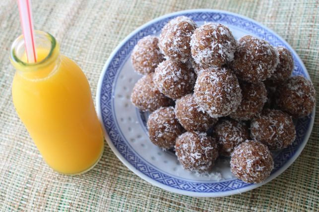 coconut and date balls on a plate next to a glass of orange juice
