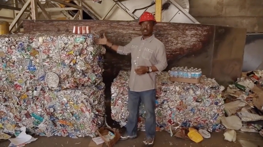 Lavar Burton stands in front of massive blocks of recycled material.