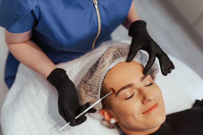 Patient with a hair net on lying on a treatment bed while Nurse Dawn applies a skin peel using a brush