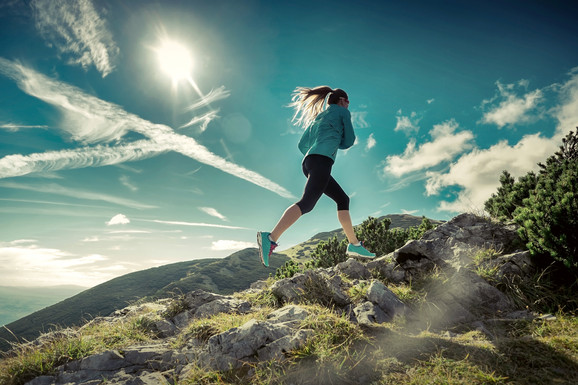 Female running in mountains under sunlig