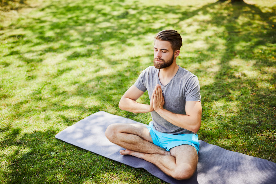 Young man meditating outdoors in the par