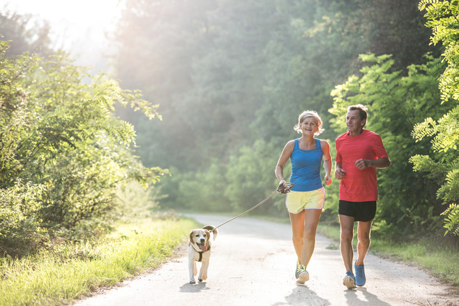 Senior couple with dog running in green