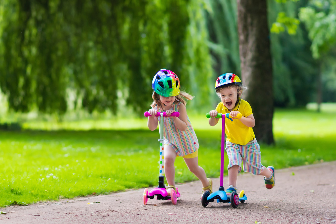 Children learn to ride scooter in a park