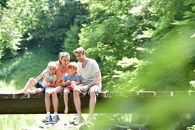 Family sitting on a bridge crossing moun