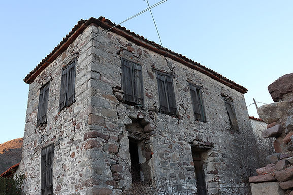 An old traditional stone house with a large yard is for sale in Eressos