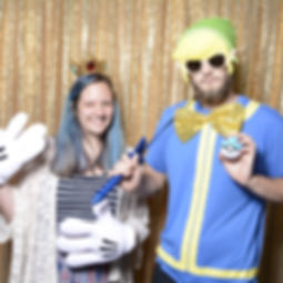 A couple dressed in a variety of props (from Disney to Legend of Zelda) posing in a photo booth with a sequin gold backdrop.
