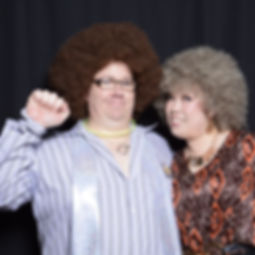 A couple dressed in 70s disco fashion posing in a photo booth with a black backdrop.