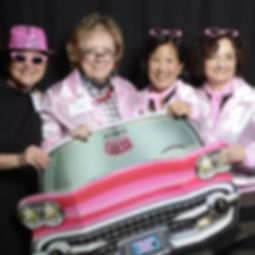 A group of 4 individuals dressed up in a pink 50s style with car cutout, posing in a photo booth.