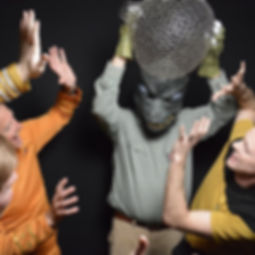 A group of guys dressed from Star Trek in a photo booth, posing like they are being attacked by the person dressed up as Gorn.