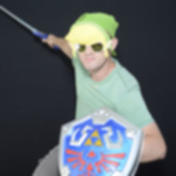 A person posing as Link with Master Sword and Hyrule Shield, in a battle ready pose, in a photo booth at Arlington Brew Festival.