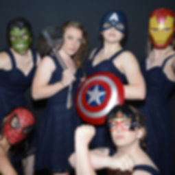 A group of bridesmaids with Avengers Masks (and Wonder Woman) posing in a wedding photo booth.