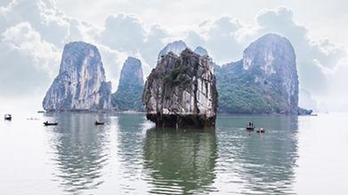 Tourist junks floating among limestone rocks at Ha Long Bay South China Sea Vietnam Southe