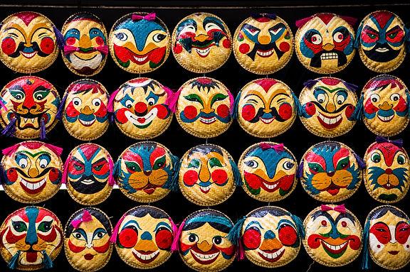 Rows of hanging face painted on woven round bamboo trays. Famous colorful straw tray masks