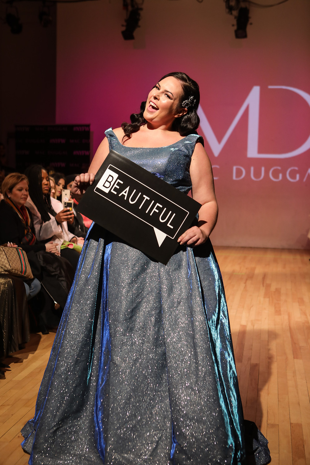 Kari walking the runway in a beautiful silver glitter gown holding a sign that says beautiful