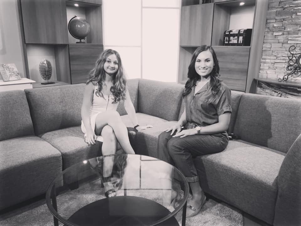 A picture of Saverina sitting on a grey couch at the Cable 14 studio in Hamilton Ontario