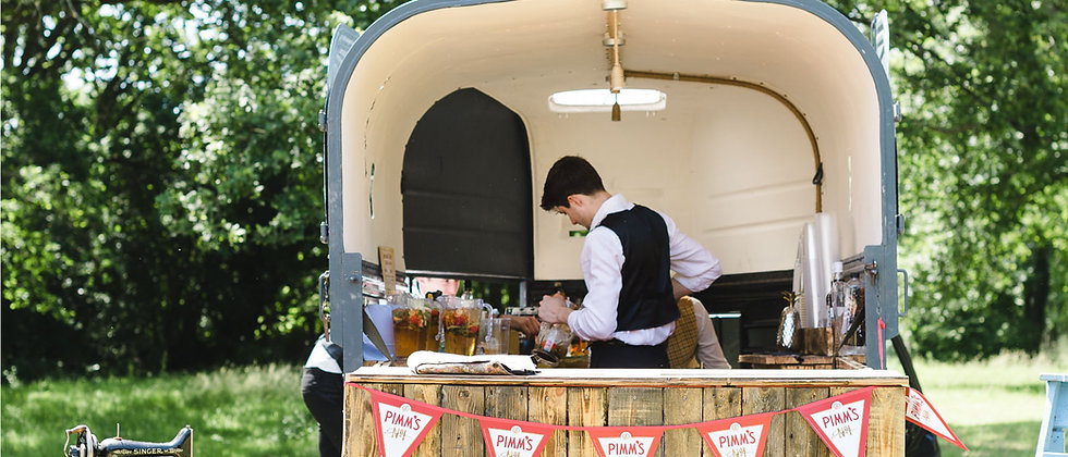 An outside view of 'Arabella,' our rustic Rice horse box mobile bar. Situated in a Summer wedding setting.