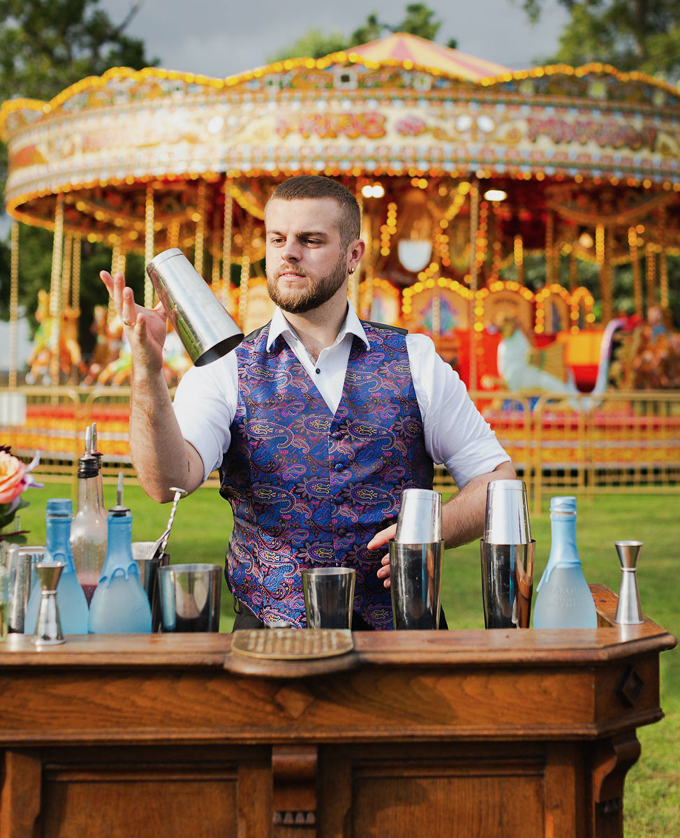 Barman behind Lectern bar catching cocktail shaker in his hand. Standing in front of fairground carousel.