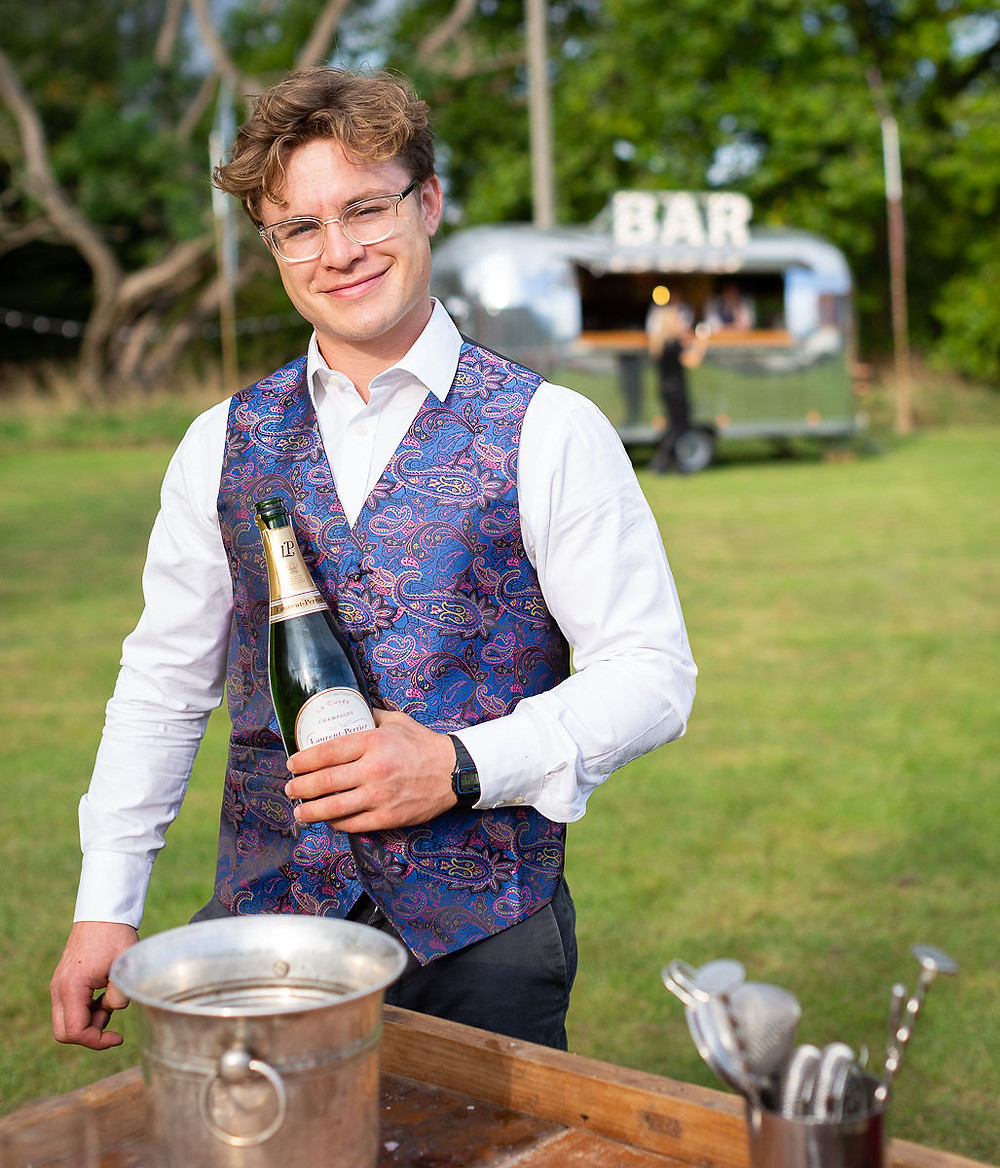 Barman smiling holding a bottle of champagne in front of airstream bar