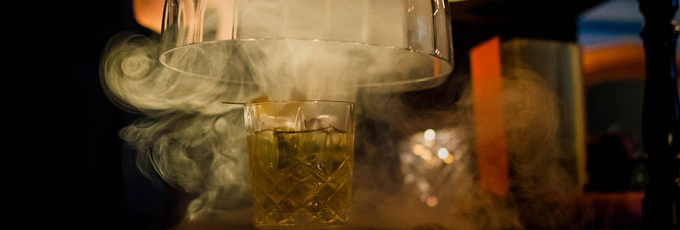 Close up view of our mixologists' whisky sour with beautiful smoke pouring onto our Tudor portable bar based in Surrey