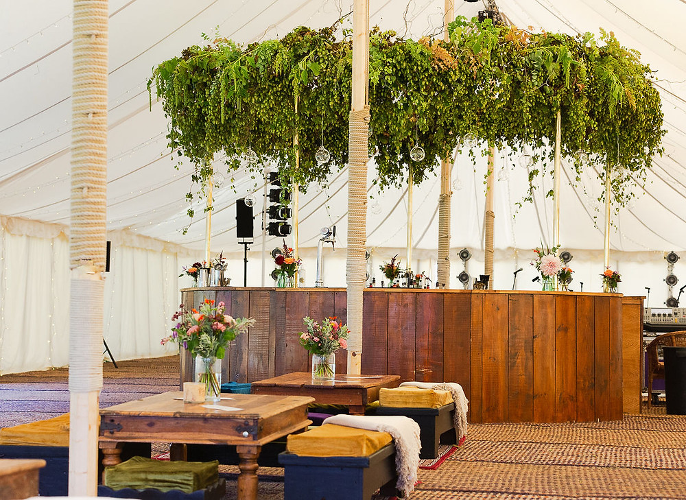 360 wooden round bar decorated with floral halo in wedding marquee