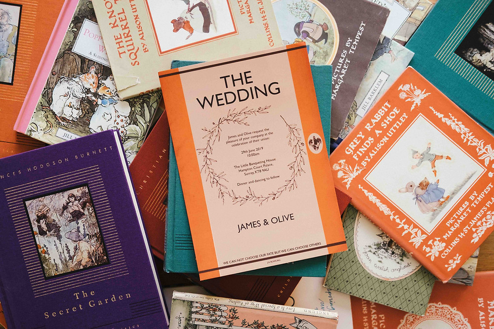 An invite laying on a stack of Penguin books