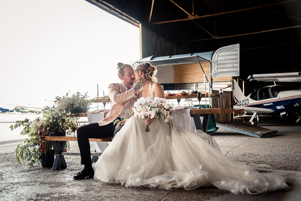 Bride and groom sat at table in front of converted horse box bar 'Arabella'.