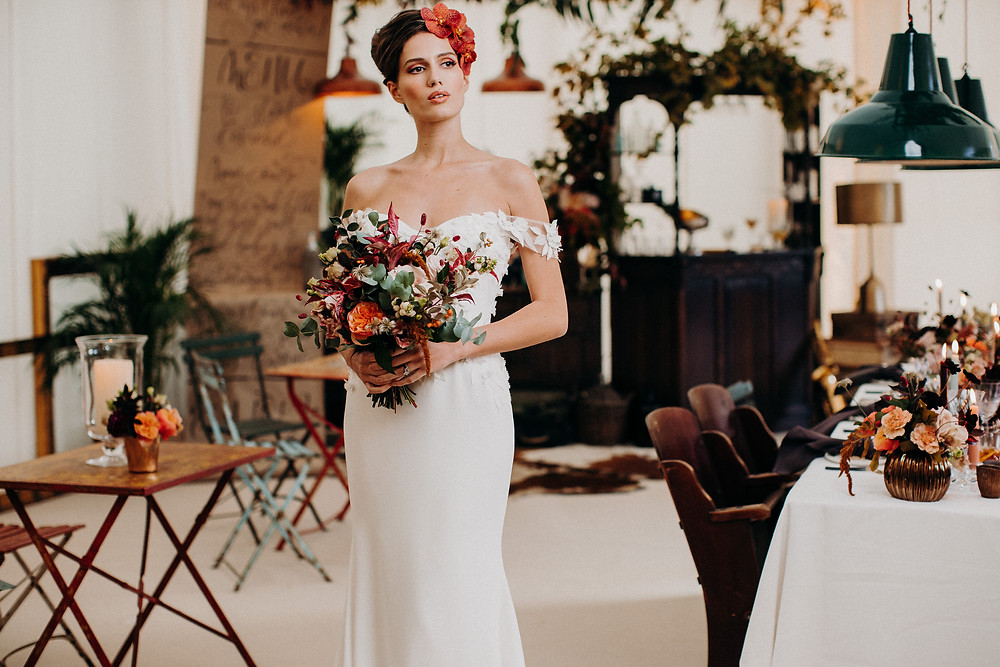 Bride with bouquet standing in front of vintage Albert bar at wedding