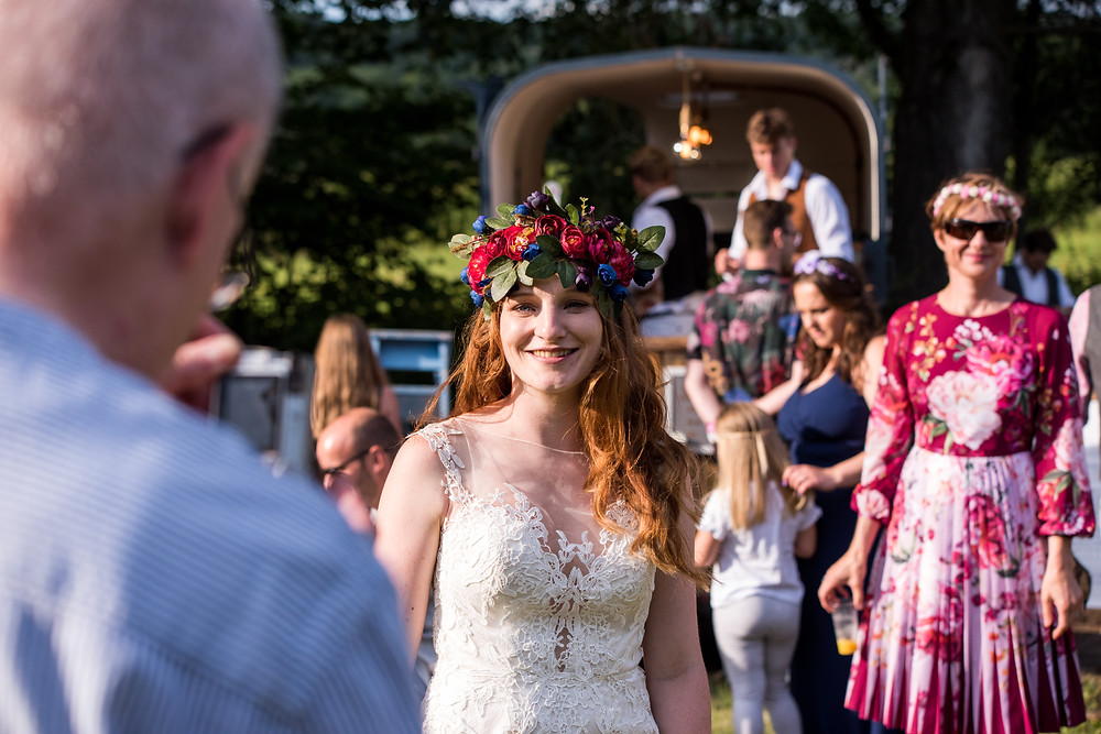 Bride in floral crown standing in front of converted horse box bar surrounded by wedding guests
